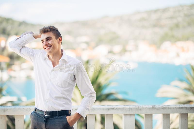 Young handsome man enjoying stay at luxury resort hotel with panoramic view on the sea stock photo