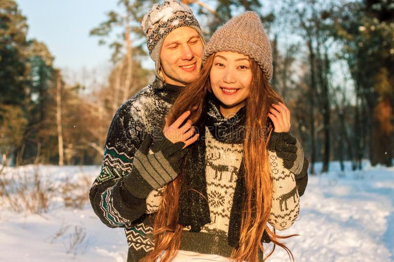 A young handsome man of European appearance and a young Asian girl in a park on the nature in winter royalty free stock photos