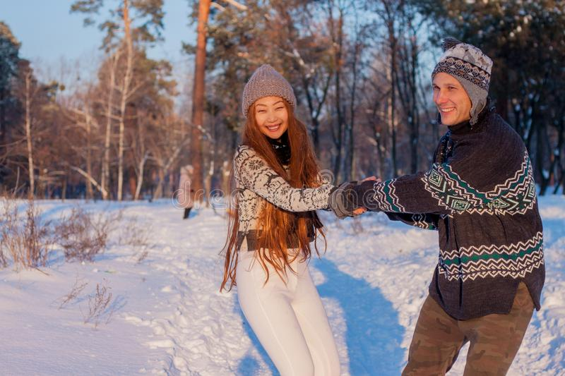 A young handsome man of European appearance and a young Asian girl in a park on the nature in winter stock image