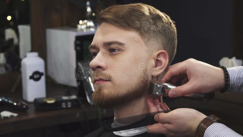 Young handsome man getting his beard trimmed by a professional barber. Close up of a handsome young men smiling while professional barber trimming his beard with stock photo