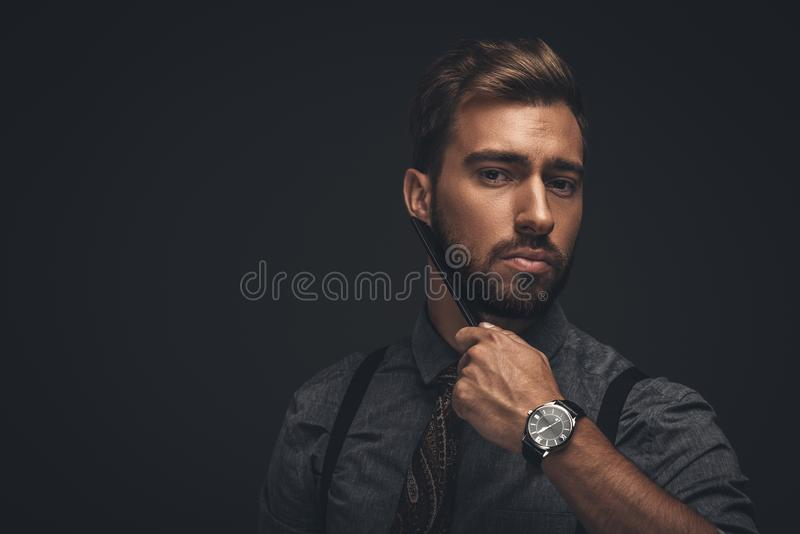 Young handsome man grooming his beard with a comb and looking. At camera stock images
