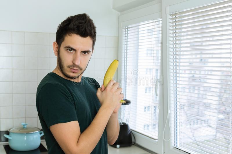 Young handsome man having fun in his kitchen. Imagining that a banana is a weapon stock photo