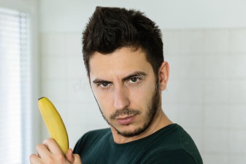 Young handsome man having fun in his kitchen. Imagining that a banana is a weapon royalty free stock photos