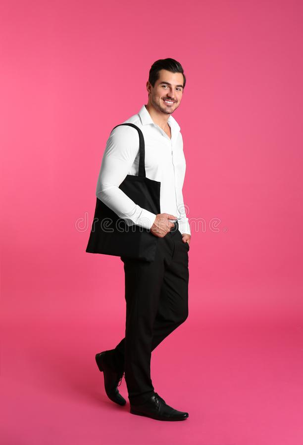 Young handsome man holding black tote bag on pink background, space for royalty free stock photography