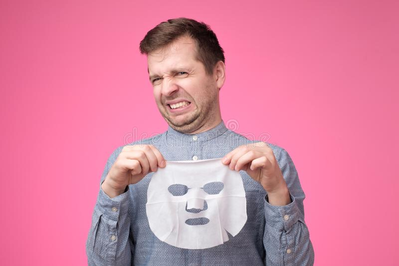 Young handsome man holding cosmetic mask and looking puzzled standing on pink background. royalty free stock image