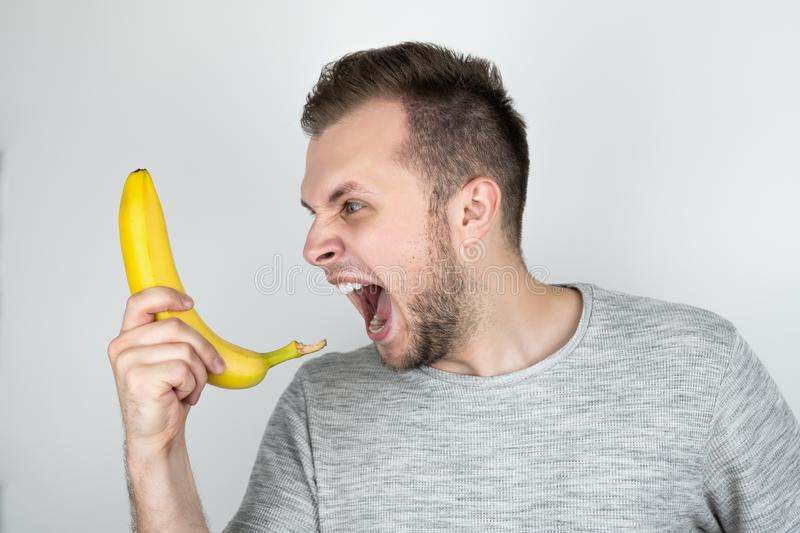 Young handsome man holding fresh banana like a smartphone screaming on isolated white background stock image