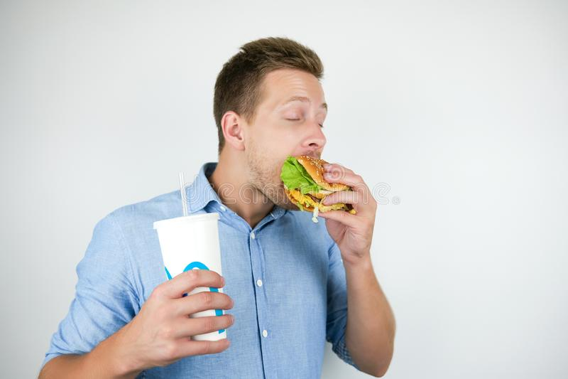 Young handsome man holding soda drink in paper cup and biting burger from fast food restaurant looks hungry on isolated. White background royalty free stock photography
