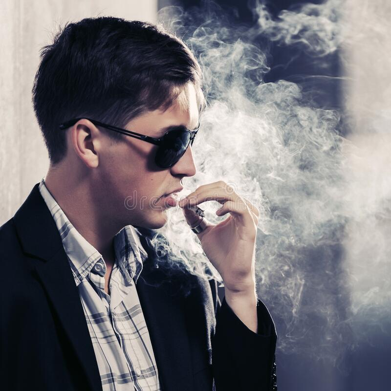 Free Young Handsome Man In Sunglasses Smoking A Cigarette Royalty Free Stock Image - 171715416