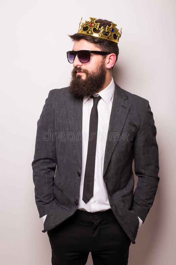 Free Young Handsome Man In Sunglasses Wearing Suit And Crown Keeping Hand On His Jacket Royalty Free Stock Image - 70129026