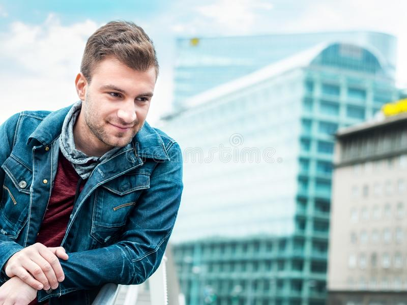 Young handsome man lookig. Gorgeous guy posing. In front modern buildings stock photos