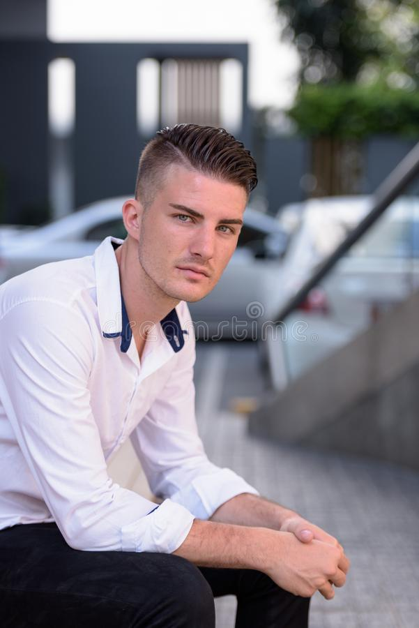 Young handsome man looking at camera while sitting outside moder royalty free stock photo