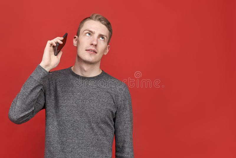Young handsome man looking up from annoying boring conversation on phone. businessman tired of constant long calls from clients. Young handsome man looking up royalty free stock photo