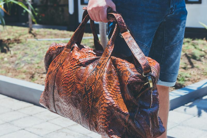 Young handsome man with luxury snakeskin python travel bag. Bali island, Indonesia. Young handsome man with luxury snakeskin python travel bag. Bali island royalty free stock images