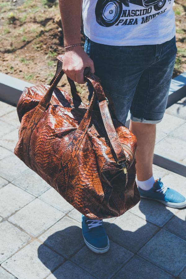 Young handsome man with luxury snakeskin python travel bag. Bali island, Indonesia. Young handsome man with luxury snakeskin python travel bag. Bali island stock photo