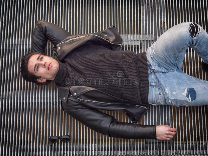 Young man on metal grid looking at camera royalty free stock image