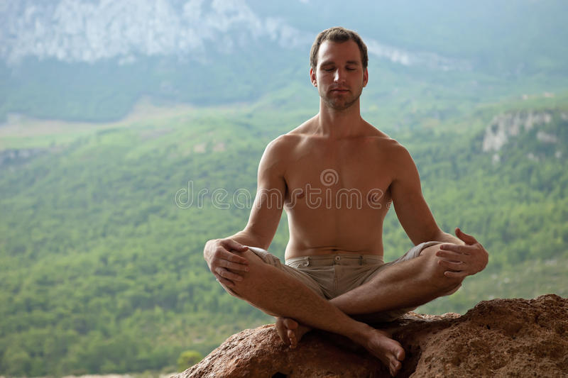Young handsome man meditating on rock royalty free stock images