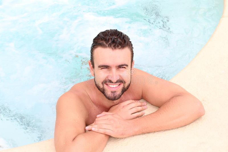 Young handsome man in outdoor jacuzzi on resort stock photo