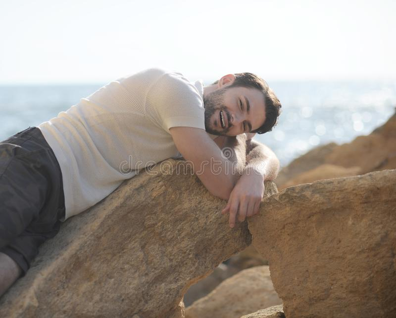 Young man outdoor portrait lying on a rocks and smiling stock photo