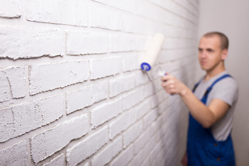 Young handsome man painter in uniform painting brick wall with p stock images