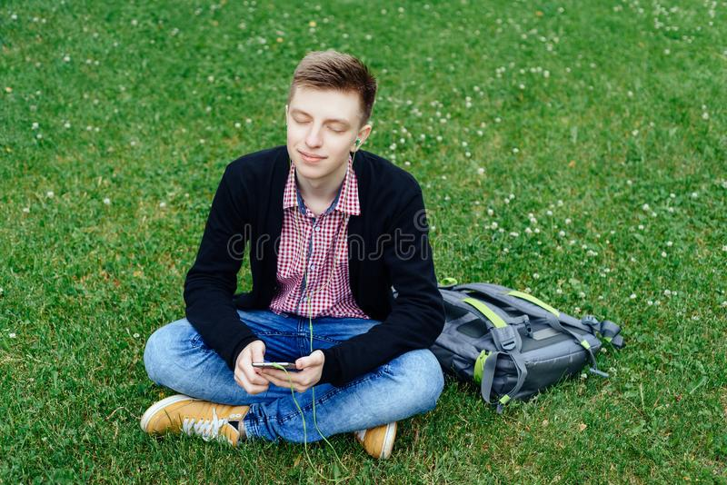 Young handsome man in plaid shirt sitting on green lawn with closed eyes and  listening to music with headphones from smart phone stock photo