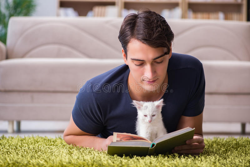 The young handsome man playing with white kitten royalty free stock image