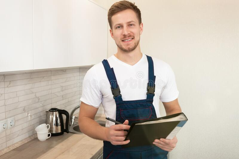 Young handsome man plumber with guarantee papers in his hands looks happy after finishing installation work in the stock image
