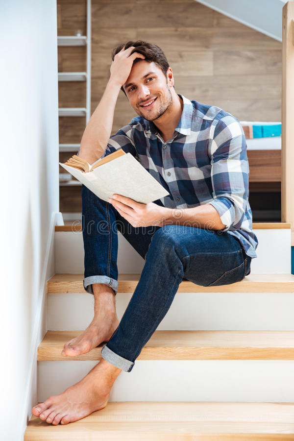 Young handsome man reading book while sitting on the stairs royalty free stock photo