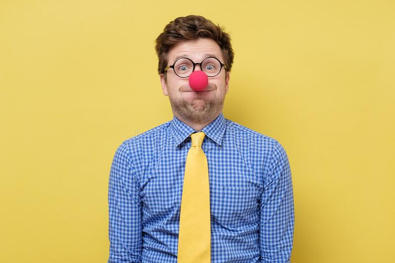 Young handsome man with red clown nose blowing cheeks. Studio shot on yellow wall royalty free stock image