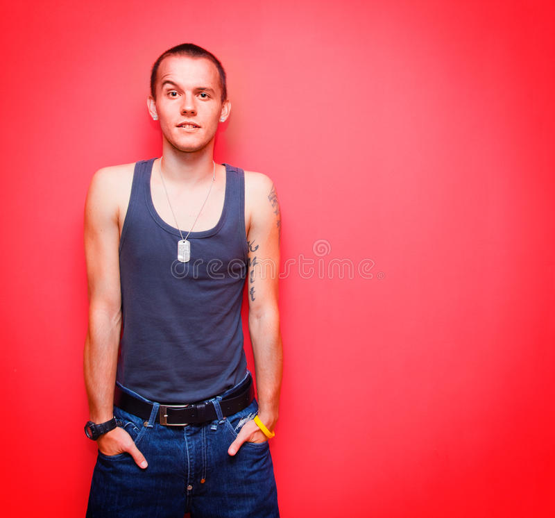 Young handsome man on red wall. Young handsome man standing in a pose on red background royalty free stock photo