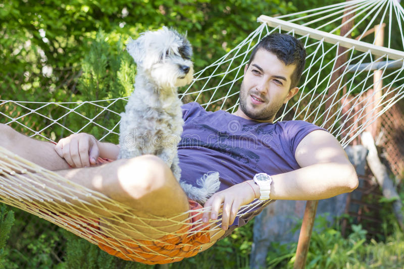 Young handsome man Relaxing In Hammock with his white dog royalty free stock images