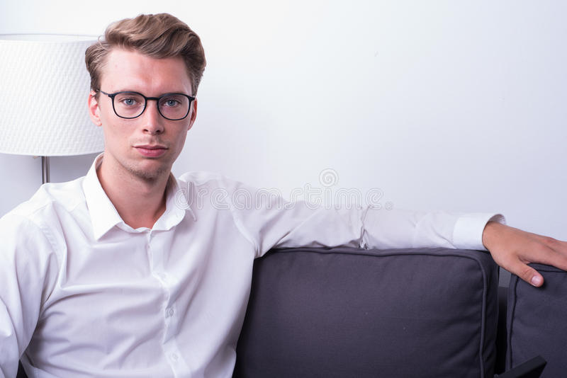 Young handsome man relaxing at home on the couch stock photos