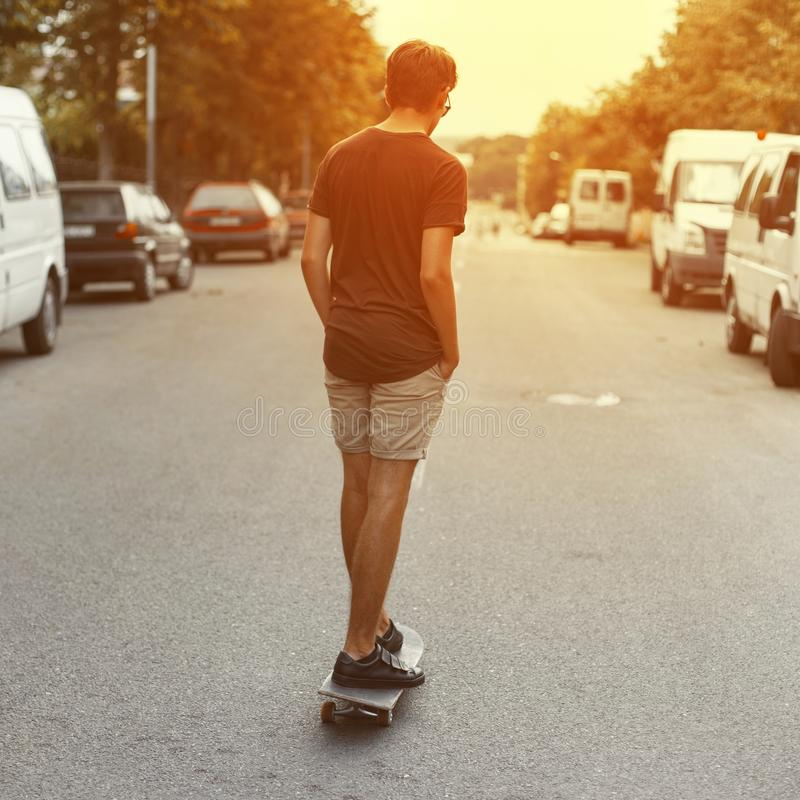 Young handsome man riding a skateboard down the street at sunset. American guy travels around the city in the summer. royalty free stock images