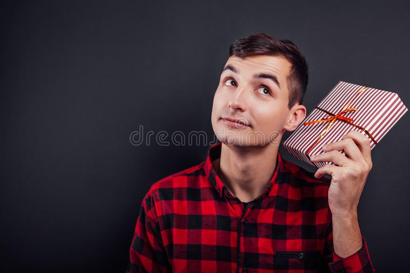 Young handsome man shakes a gift box to find out what`s in it royalty free stock photo