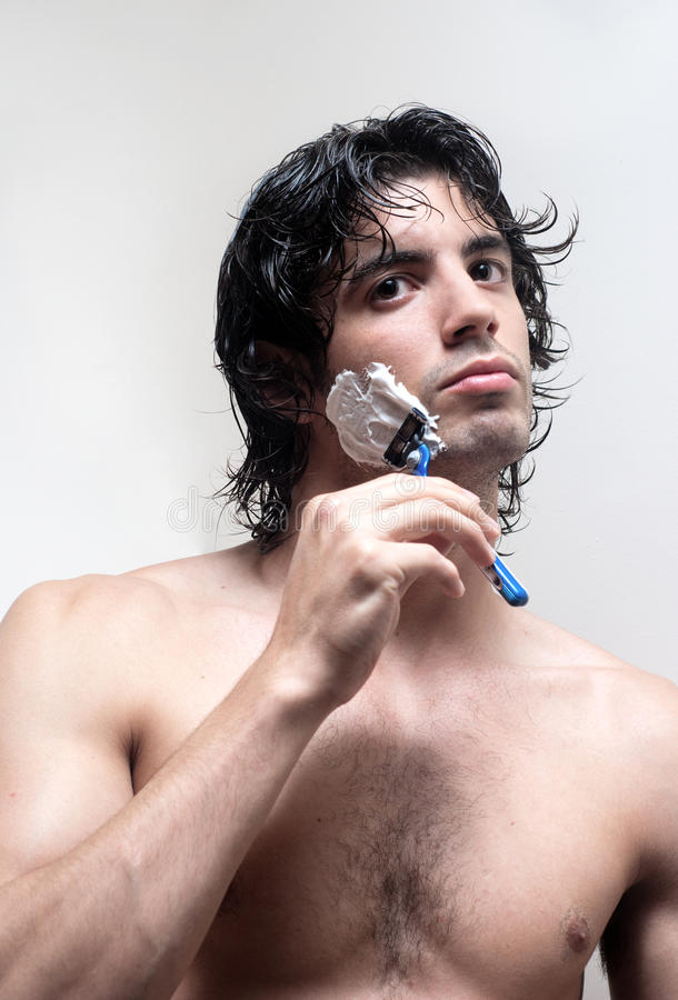 Young handsome man shaving stock photo