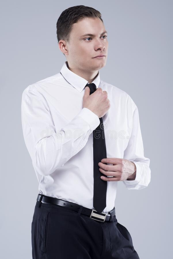 Young handsome man in a shirt with a tie on a light gray background stock image