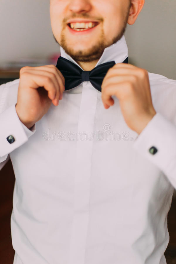 Young handsome man with short beard dressing bow tie in his hand stock photography