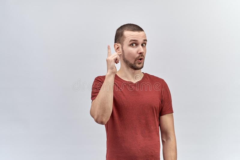 Young handsome man with short hair and a surprised expression understands a thumbs up. concept of insight, ideas, solutions. stock images