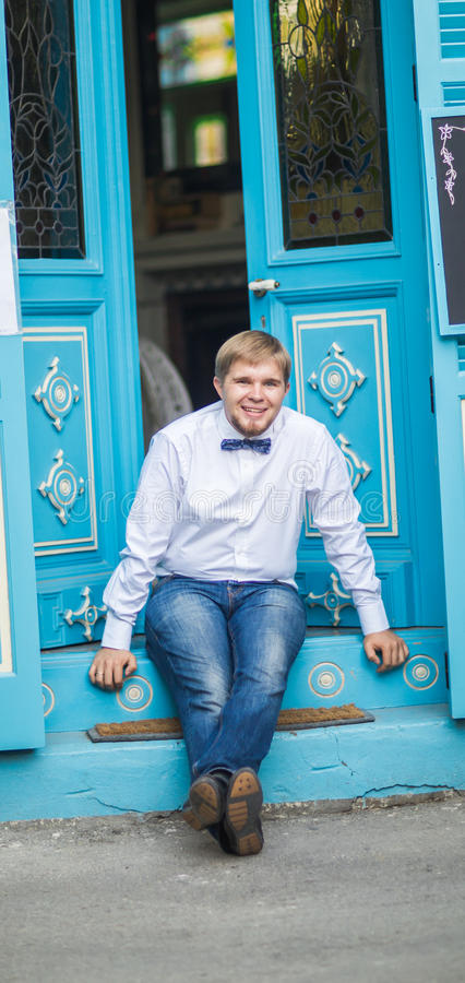 Young handsome man with short hair wearing a bow tie and posing in the city streets. royalty free stock image