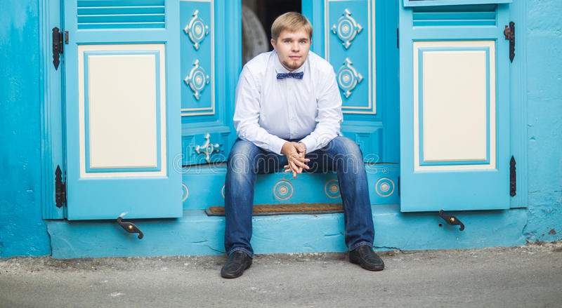 Young handsome man with short hair wearing a bow tie and posing in the city streets. stock photos