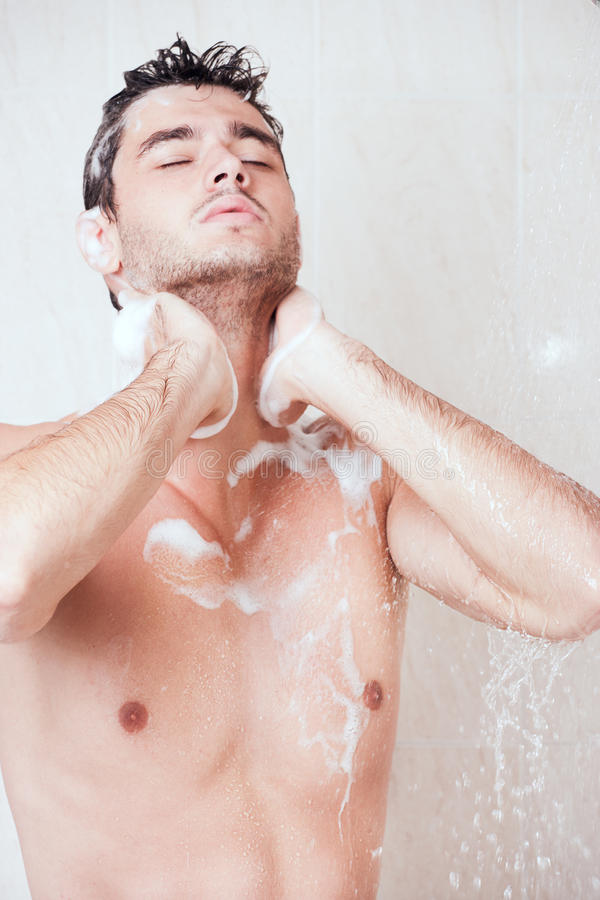 Young handsome man in shower. Young handsome man washing head with shampoo in shower stock image
