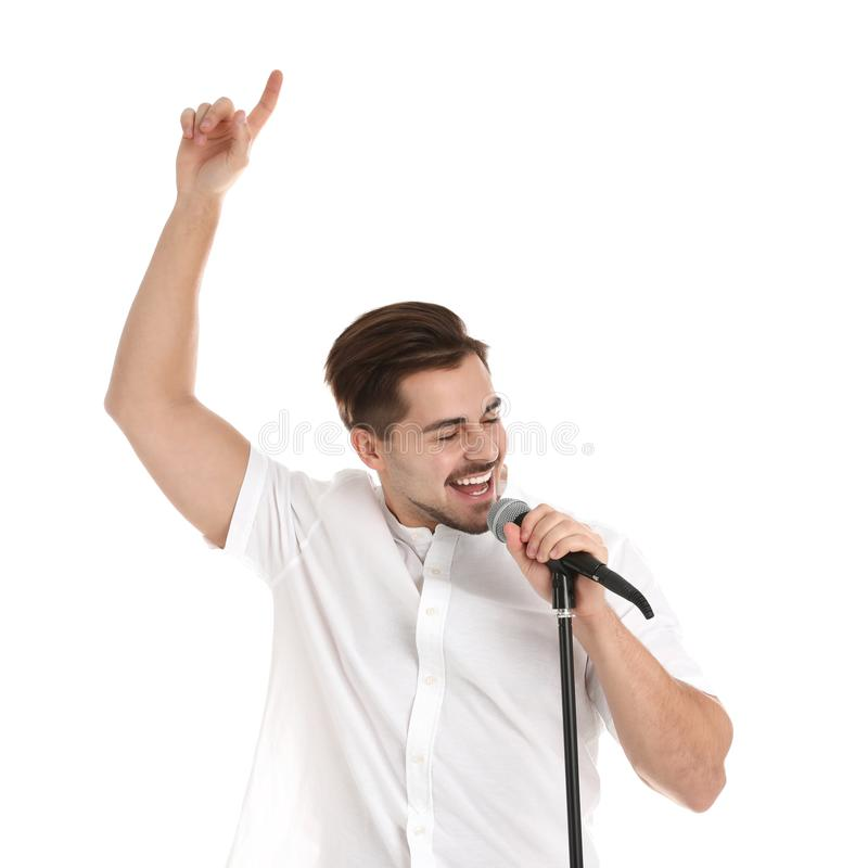 Young handsome man singing in microphone on white. Background royalty free stock image