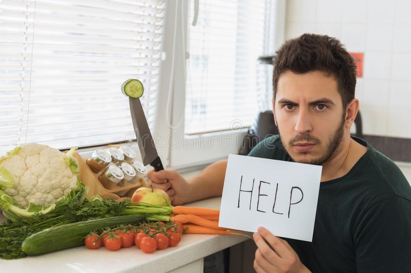 A young handsome man sits in the kitchen with an angry face and asks for help. The guy does not want to go on a healthy lifestyle and eat fresh vegetables royalty free stock image