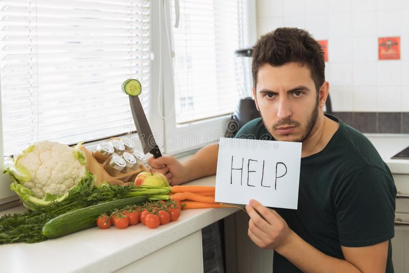 A young handsome man sits in the kitchen with an angry face and asks for help. The guy does not want to go on a healthy lifestyle and eat fresh vegetables royalty free stock photography