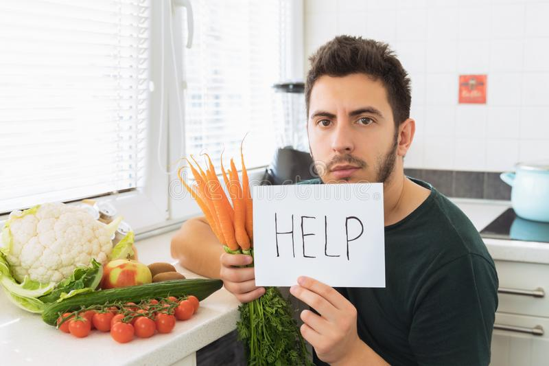A young handsome man sits in the kitchen with an angry face and asks for help. The guy does not want to go on a healthy lifestyle and eat fresh vegetables royalty free stock photo