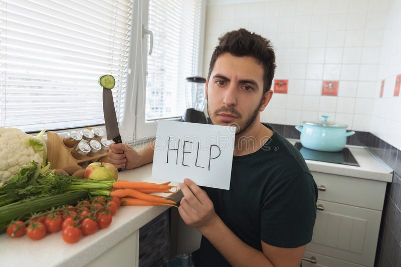 A young handsome man sits in the kitchen with an angry face and asks for help. A young handsome man sits in the kitchen with a sad face and asks for help. The royalty free stock photo