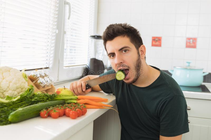 A young handsome man sits in the kitchen and reluctantly eats vegetables. The guy does not want to go on a healthy lifestyle and eat healthy food royalty free stock photos