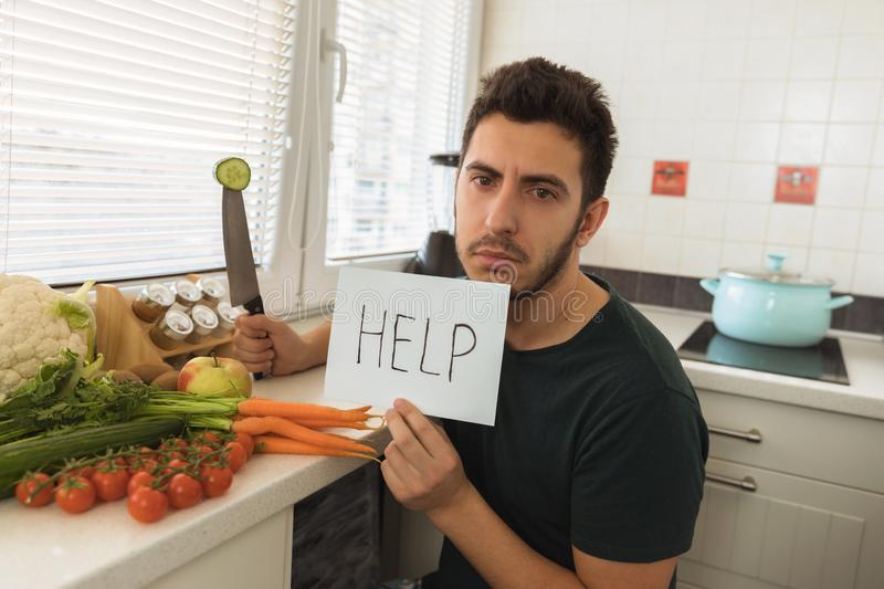 A young handsome man sits in the kitchen with a sad face and asks for help. The guy does not want to go on a healthy lifestyle and eat fresh vegetables stock photo