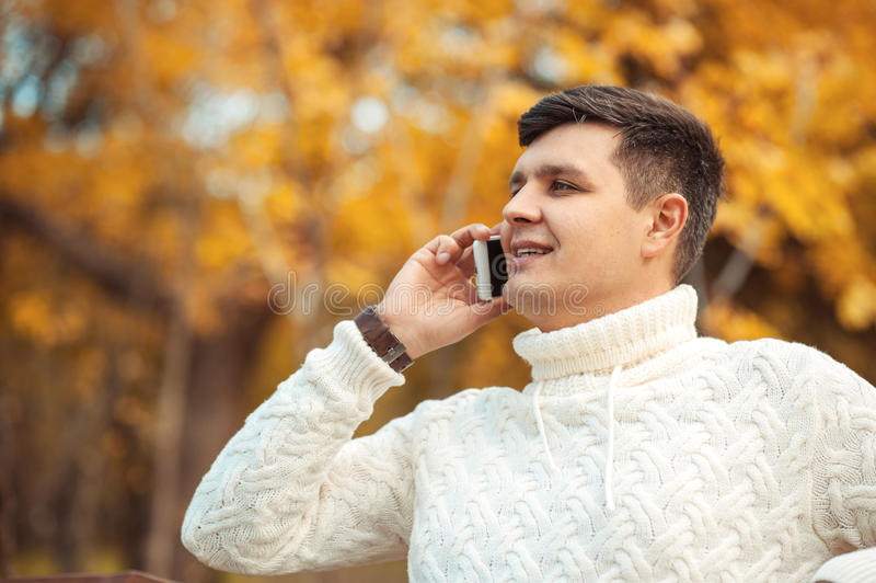 Young handsome man sitting in autumn park and talking by phone. Businessman is calling to someone by smartphone royalty free stock photo