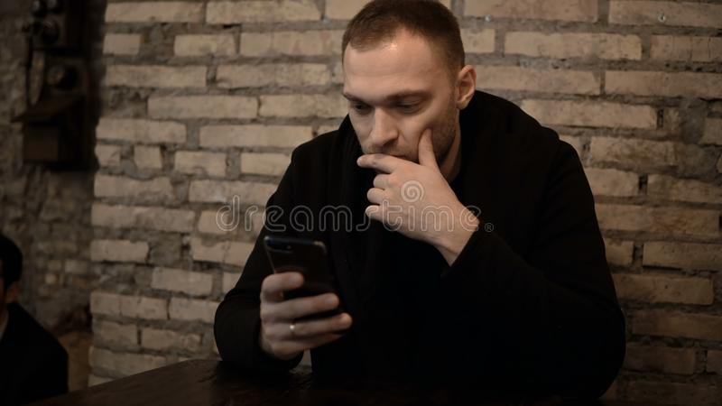 Young handsome man sitting in the cafe with brick wall and using the smartphone, browsing the Internet alone. stock photo