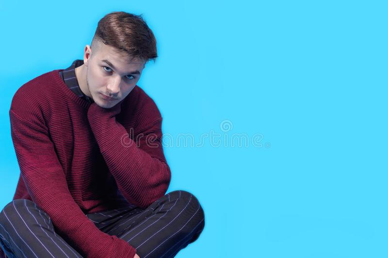 Young handsome man sitting on the floor on blue background.  Fashion hairstyle, expressive harsh look to the camera. royalty free stock photo